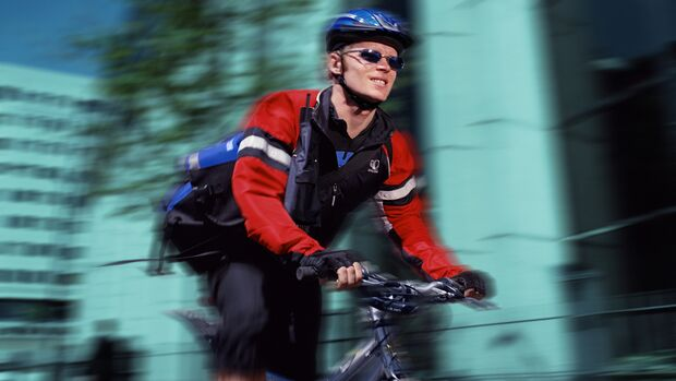 Male cycle courier riding along city street (Digital Composite)