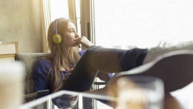 Relaxed young woman sitting on a chair wearing headphones